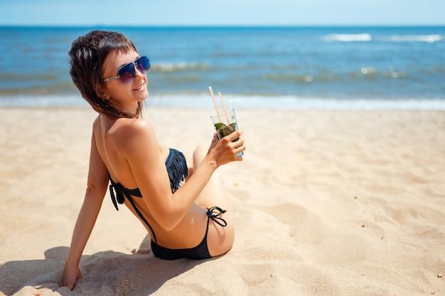 Donna che tiene vetro del cocktail fresco di mojito sulla spiaggia