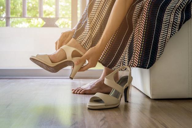 Donna che toglie le scarpe con i tacchi alti