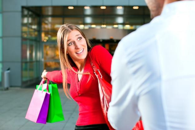 Donna che trascina uomo nel centro commerciale