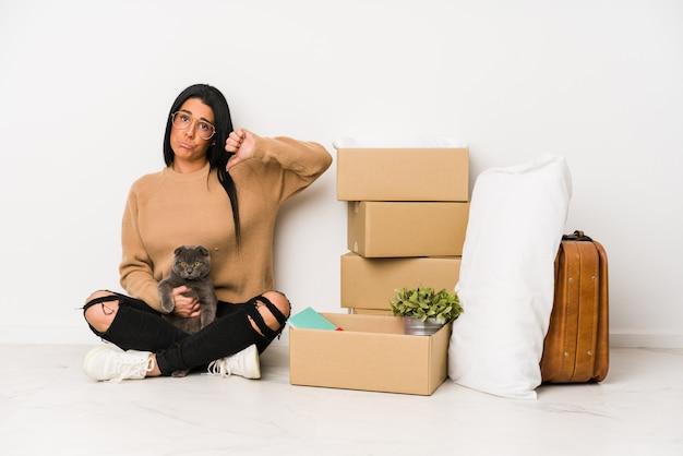 Donna che trasloca a casa su bianco che mostra un gesto di avversione, pollici giù. concetto di disaccordo.