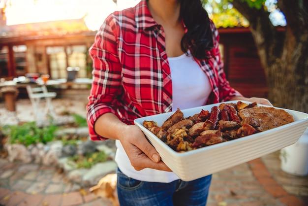 Donna che trasporta una ciotola con carne barbecue