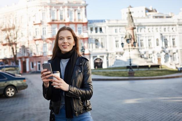 Donna che trova la sua strada in città. ritratto della femmina caucasica affascinante in attrezzatura d'avanguardia che cammina sulla via