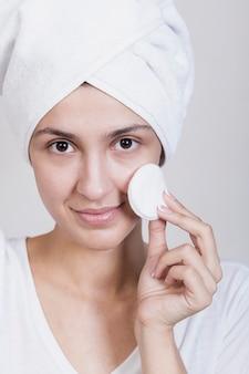 Donna che usando i dischetti di cotone