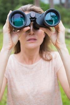Donna che usando il binocolo