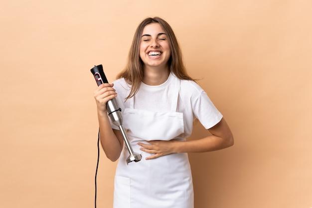 Donna che usando il miscelatore della mano sopra la parete isolata che sorride molto