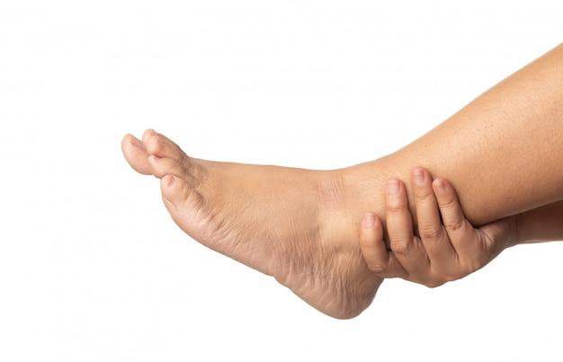 Donna che usando la gamba della tenuta della mano e massaggiandola dolorosa.