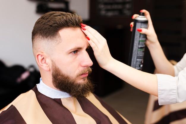 Donna che usando lacca per capelli sul suo cliente