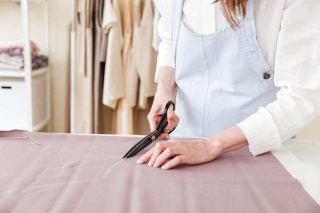 Donna che usando le forbici per tagliare il tessuto