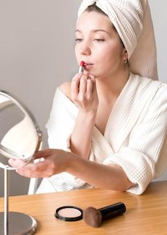 Donna che usando specchio per applicare il rossetto
