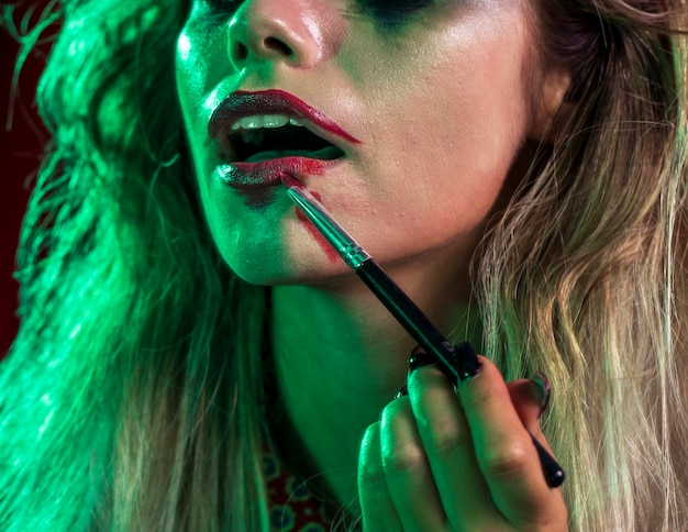 Donna che usando un pennello per rossetto