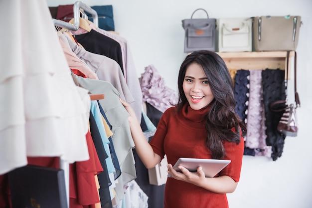 Donna che utilizza compressa digitale nel negozio di vestiti