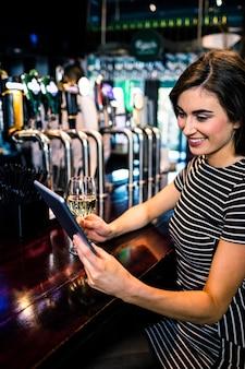 Donna che utilizza compressa e che mangia un bicchiere di vino in una barra