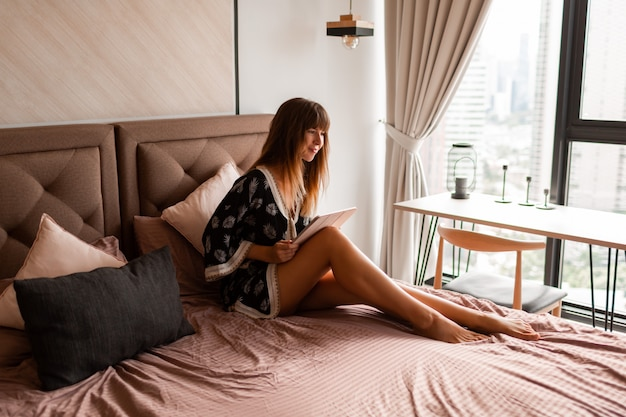 Donna che utilizza compressa e che si rilassa a letto