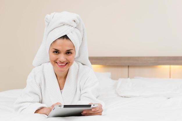 Donna che utilizza compressa nella camera d'albergo