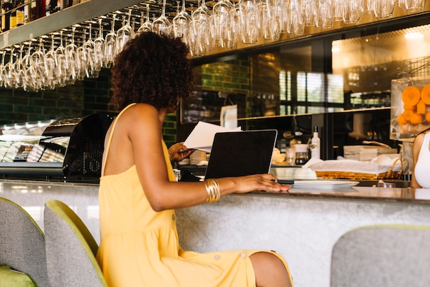 Donna che utilizza computer portatile al bancone del bar nel ristorante