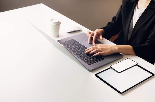 Donna che utilizza computer portatile e tablet, telefono immessi sul tavolo, mock up di schermo vuoto.