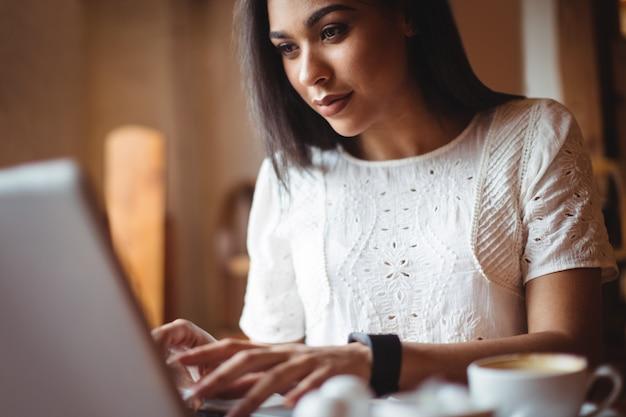 Donna che utilizza computer portatile nel café