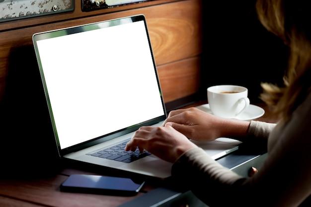 Donna che utilizza computer portatile sulla scrivania in mattinata