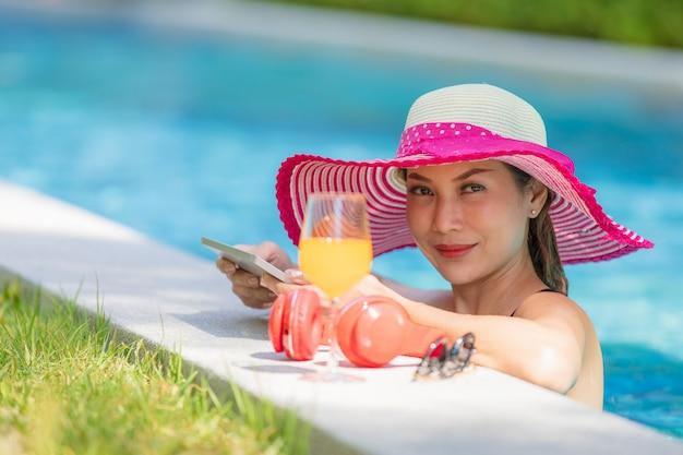 Donna che utilizza computer tablet in piscina