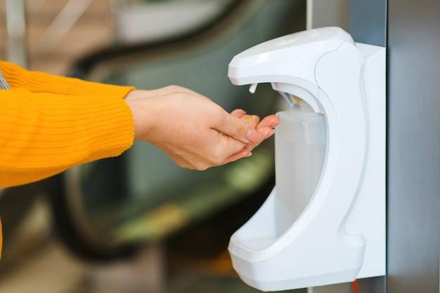 Donna che utilizza gel antisettico in un centro commerciale per prevenire la diffusione di germi, batteri, coronavirus e virus.