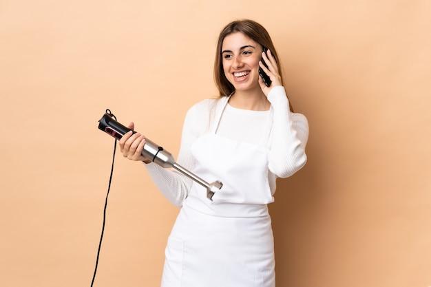 Donna che utilizza il frullatore a immersione mantenendo una conversazione con il telefono cellulare