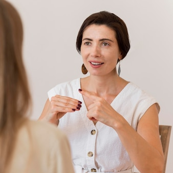 Donna che utilizza il linguaggio dei segni per comunicare con la sua amica