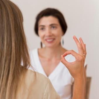 Donna che utilizza il linguaggio dei segni per conversare con la sua amica