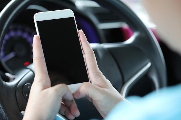 Donna che utilizza il telefono cellulare in macchina.