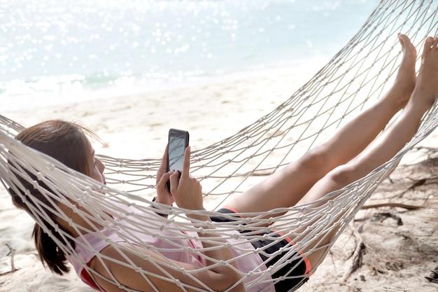 Donna che utilizza il telefono cellulare sull'amaca accogliente maglia in spiaggia.