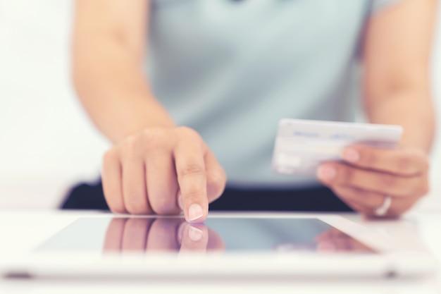 Donna che utilizza la compressa e carta di credito per il pagamento online banking e acquisti