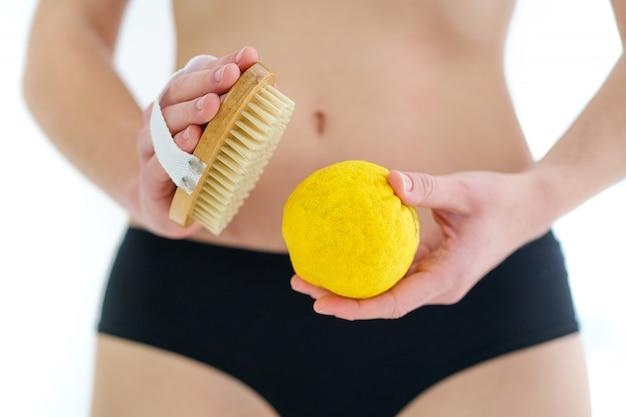 Donna che utilizza la spazzola di legno asciutta per massaggiare e spazzolare la pelle per prevenire e curare la cellulite e i problemi del corpo a casa. salute della pelle