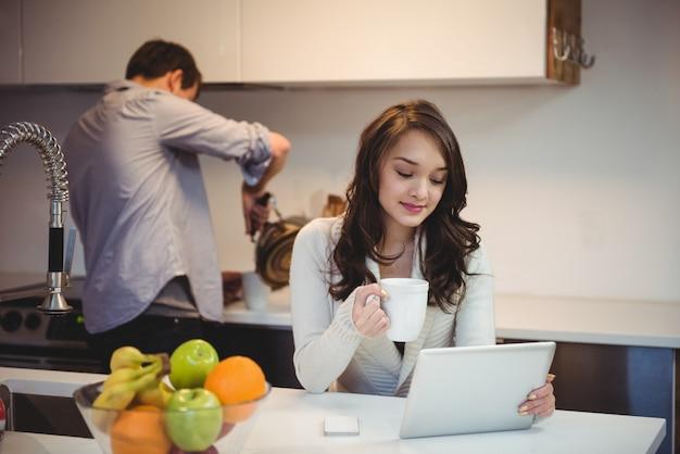 Donna che utilizza la tavoletta digitale mentre l'uomo che lavora in background