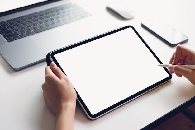 Donna che utilizza lo schermo del tablet vuoto e il computer portatile sul tavolo che simula per promuovere i tuoi prodotti