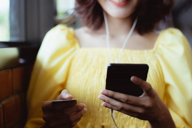 Donna che utilizza smartphone che ascolta la musica nel tempo libero con felice.