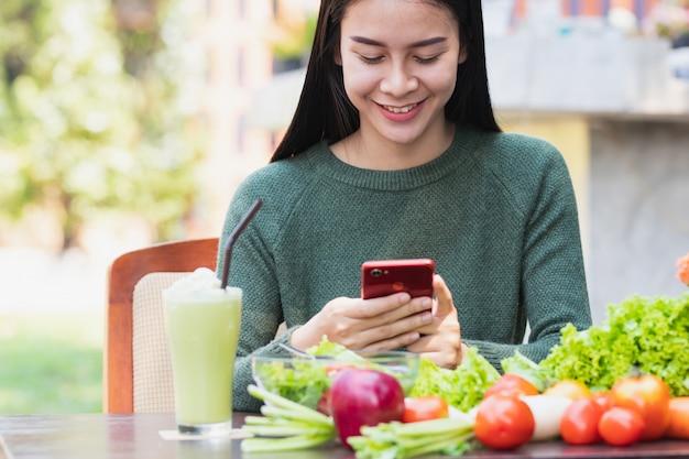 Donna che utilizza smartphone e mangiare cibo sano con felice.