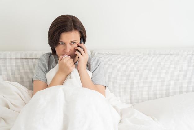 Donna che utilizza smartphone mentre si siede nel letto coperto di piumone, spaventato e terrorizzato