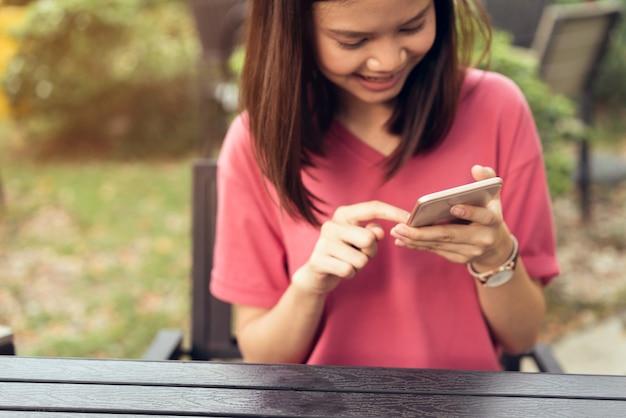 Donna che utilizza smartphone per l'applicazione sul tavolo in park cafe. concetti per la tecnologia digitale