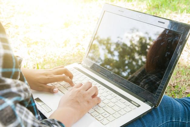 Donna che utilizza un computer portatile al parco