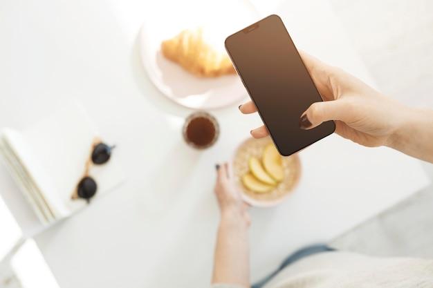 Donna che utilizza un telefono per scattare una foto del suo pasto