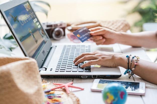 Donna che utilizza una carta di credito e un computer portatile