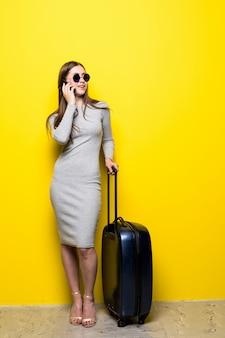 Donna che va in viaggio e parla al telefono sopra la parete gialla