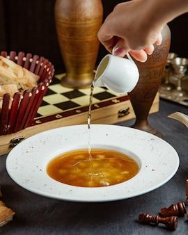 Donna che versa aceto nella zuppa di gnocchi di dushbara