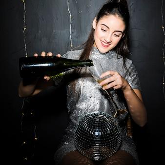 Donna che versa champagne in vetro vicino a palla da discoteca