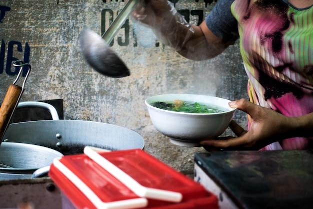 Donna che versa la deliziosa zuppa vietnamita tradizionale pho in una ciotola
