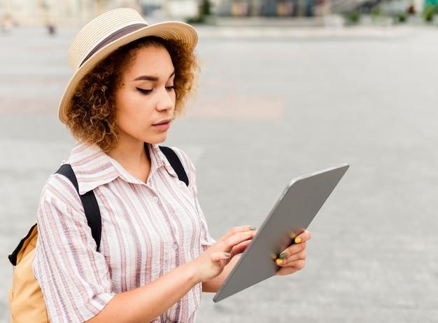 Donna che viaggia alla ricerca di indicazioni stradali su un tablet