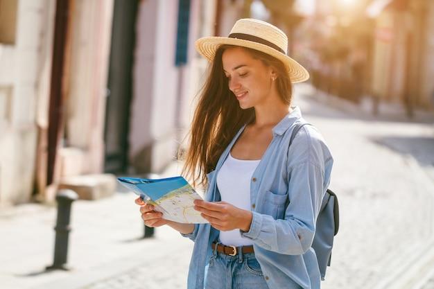 Donna che viaggia in cappello alla ricerca della giusta direzione sulla mappa di viaggio durante il viaggio in europa. stile di vita per vacanze e viaggi