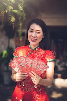 Donna cinese asiatica che indossa il vestito rosso tradizionale cheongsam che tiene busta rossa