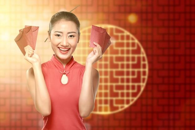 Donna cinese asiatica in un vestito dal cheongsam che tiene le buste rosse