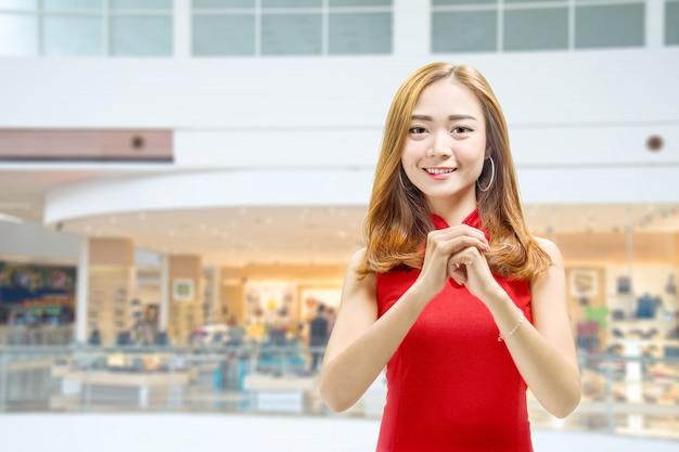 Donna cinese asiatica in un vestito dal cheongsam con il gesto di congratulazioni