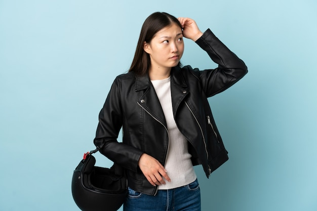 Donna cinese che tiene un casco del motociclo sopra la parete blu che ha dubbi e con l'espressione confusa del fronte